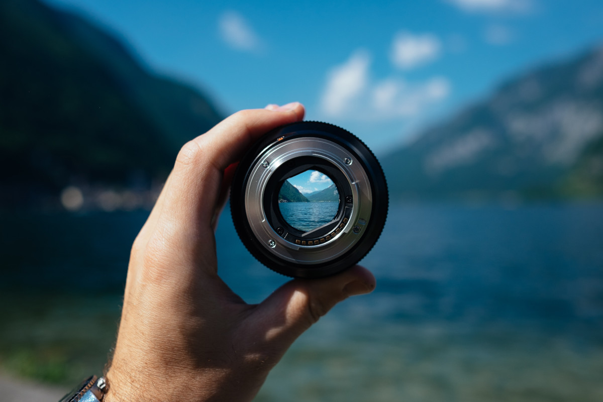 Person holding camera lens photo - used, with permission, from Unsplash.