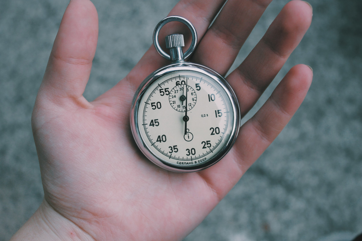 A hand holding a stop watch, representing an audit for a webpage load speed
