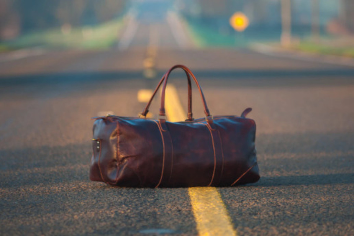 A single, brown leather travel bag in the middle of the road